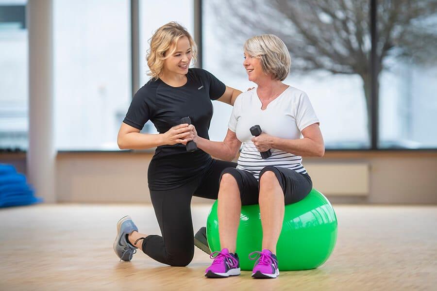 Frau trainiert auf einem Ball mit Anweisungen einer Trainerin im Fitnessstudio Darmstadt