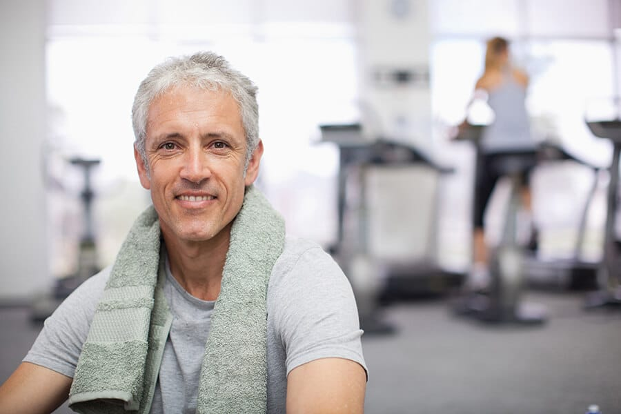 Älterer gesunder Mann mit einem Handtuch im Fitnessstudio Darmstadt beim Rehasport
