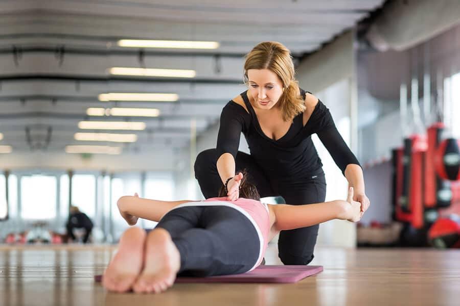 Frau und Trainerin beim medizinischen Rückentraining im intenso
