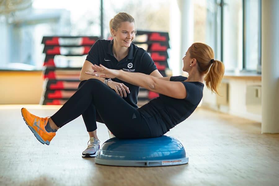Frau und Trainerin auf einem Pezziball beim Medical Training