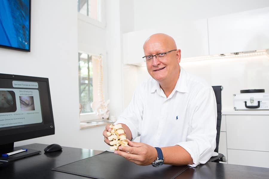 Dr Danneberg mit einem Modell der Wirbelsäule