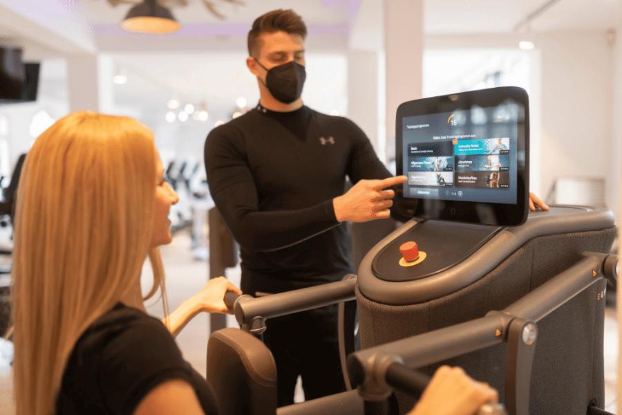 Trainer mit Maske erklärt das digitale Training